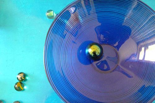 Murmeln streben in eine blaue Glasschale